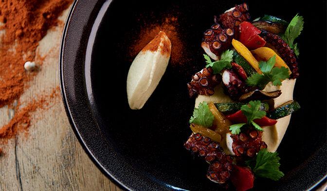 Poulpe grillé au paprika, purée de pois chiche persillée et légumes grillés