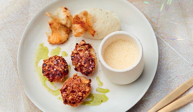 Noix de coquille Saint-Jacques poêlées en croûte de noisette, mousseline de chou-fleur, jus de persil et émulsion d'ail